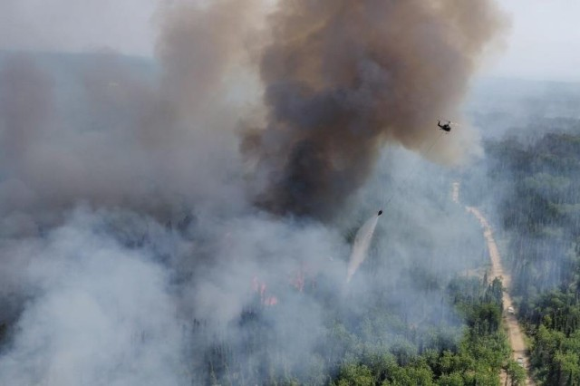 Two Alaska Army National Guard UH-60 Black Hawk helicopters and aircrew from 1st Battalion, 297th Aviation perform Bambi bucket water drops over the Montana Creek Fire, July 4, 2019.