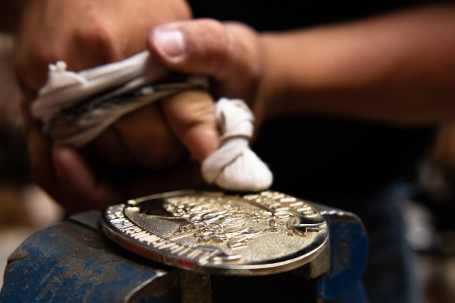 A Soldier assigned to the Fort Sill Artillery Half Section buffs up a Half Section belt buckle getting it ceremonially shiny. Each Soldier receives the buckle, a T-shirt, and cap signifying they passed the trial period and are part of the Half Section.