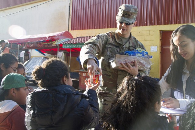 U.S. Army Reserve Sgt. Christopher Bernard of the Lubbock, Texas-based 413th Civil Affairs Battalion, hands out juice and cookies to those waiting in line to receive free medical and dental care as part of a medical readiness training exercise during exercise Beyond the Horizon. Beyond the Horizon is a joint annual training exercise that combines medical, dental, veterinary and engineering missions to improve the operational readiness of U.S. Forces and reinforce regional stability and interoperability with allied forces, resulting in tangible benefits to the people of Guatemala.