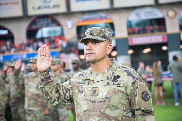1st Sgt. David O. Rodriguez Jr., Headquarters and Headquarters Company, 13th Expeditionary Sustainment Command, recites the Oath of Enlistment during a ceremony at Minute Maid Park in Houston, Texas, July 5.   In front of a sold-out crowd of 41,000 screaming fans, 80 Soldiers from units across Fort Hood, Texas, raised their right hands and recommitted themselves to protecting the nation. (U.S. Army photo by Sgt. 1st Class Kelvin Ringold)