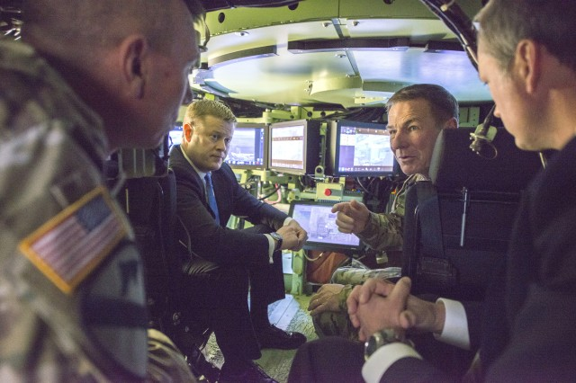 Under Secretary of the Army Ryan D. McCarthy, center left, and Gen. James C. McConville, the Army's vice chief of staff, center right, discuss emerging technology while inside a Mission Enabler Technologies-Demonstrator, a modified Bradley Fighting Vehicle equipped with several upgrades, in Warren, Mich., Jan. 18, 2018. Soldiers are slated to test two MET-Ds and four robotic combat vehicles for the first time next year.