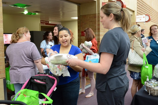 Hilda Alicia Cruz receives an infant sleep sack from Lindsey Karim, a licensed practical nurse from the EACH Mother Baby Unit, during the Fort Carson 2019 Baby Expo on June 22, 2019. Cruz attended with her daughter, Adriana Rose, who was born at EACH three months ago.