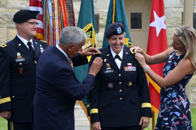 Donald Roman Sr., left, and Rebecca Roman add shoulder boards reflecting the new rank of Brig. Gen. Christine Beeler as Maj. Gen. Paul Pardew looks on during a promotion ceremony July 9 at Joint Base San Antonio-Fort Sam Houston, Texas. Donald is the father of the commanding general for the Mission and Installation Contracting Command, and Rebecca is her sister. Pardew, who officiated the ceremony, is the commanding general for the Army Contracting Command at Redstone Arsenal, Alabama.