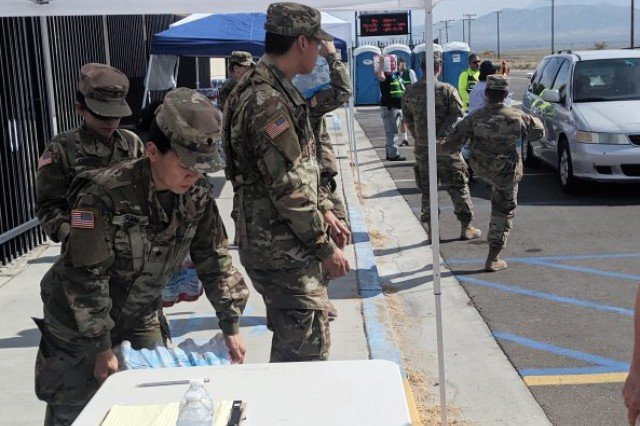 Members of the California National Guard's 143rd Military Police Battalion distribute food and water to residents of Trona, Calif., July 7, 2019 following a 7.1 magnitude earthquake Friday night that burst water lines and closed stores.
