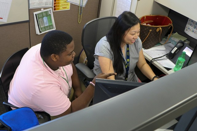 Devin Simmons, a Security Assistance Command student trainee, works with Summer Paquette, the country program manager for Brazil.