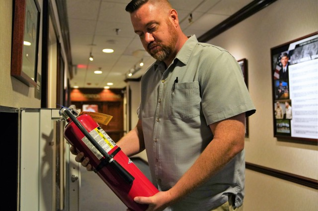 Michael Burgess, assistant facility and safety manager, U.S. Transportation Command, evaluates a fire extinguisher during a safety inspection July 9 on the third floor of Building 1900 East.