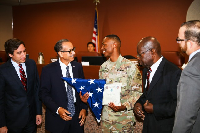 Sgt. Laderius Beattie, of Rosedale Mississippi, a human resources specialist assigned to Headquarters and Headquarters Battalion, 1st Armored Division, receives a flag and a certificate noting his exemplary service by, from left, Commissioners Vincent Perez, Carlos Leon, Carl L. Robinson and David Stout, representing Precincts 3, 1, 4 and 2, respectively, at the El Paso County Commissioners Court, July 8, in El Paso, Texas. Commissioners presented the flag, previously flown over the county courthouse from May 21 to May 27, 2019, to Beattie in front of members of the greater El Paso community during an open meeting of the El Paso Commissioners Court.