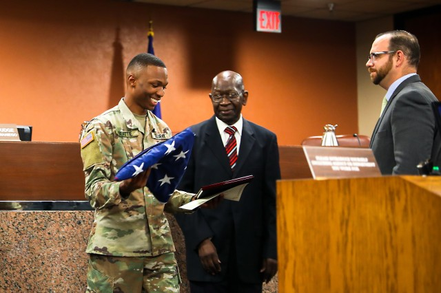 Sgt. Laderius Beattie, of Rosedale, Mississippi, a human resources specialist assigned to Headquarters and Headquarters Battalion, 1st Armored Division, reacts after receiving a certificate, plaque and a flag flown over the county courthouse from Commissioner Carl L. Robinson, center, the representative of El Paso County's Precinct 4, as Commissioner David Stout, the representative of Precinct 2, looks on at the El Paso County Commissioners Court, July 8, in El Paso, Texas. Beattie, the 1AD Warrior of the Year for 2019, addressed the court on the nature of his service prior to the court's formal recognition of his exemplary service, duty and professionalism as a Soldier in the United States Army.