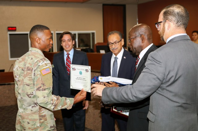Sgt. Laderius Beattie, of Rosedale, Mississippi, a human resources specialist assigned to Headquarters and Headquarters Battalion, 1st Armored Division, receives a certificate noting his exemplary service as a Soldier in the United States Army along with a plaque and a flag previously flown over the county courthouse by, from left, Commissioners Vincent Perez, Carlos Leon, Carl L. Robinson and David Stout, of Precincts 3, 1, 4 and 2, respectively, July 8, in El Paso, Texas. 1AD announced Beattie as the 1AD Warrior of the Year for 2019 in May after a series of challenging tasks and tests assessing Soldier knowledge, skills and aptitude, embodying the spirit, competence and excellences which defines the American Soldier.