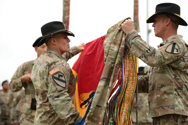 Col. Kevin Capra, left, Commander of the 3rd Armored Brigade Combat Team, 1st Cavalry Division, and Command Sgt. Maj. Ryan McLane, the 3rd ABCT, 1st Cav CSM, uncase the colors from the Transfer of Authority ceremony on Camp Humphreys, Republic of Korea June 11. Greywolf assumed the nine-month rotational brigade mission from 3rd Armored Brigade, 1st Armor Division.