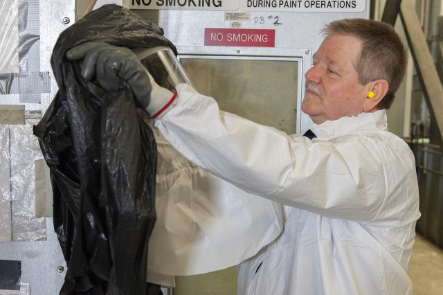 Charles Pearl uncovers his painting hood in preparation for suiting up. Personal protective equipment is an important aspect of painting safety.