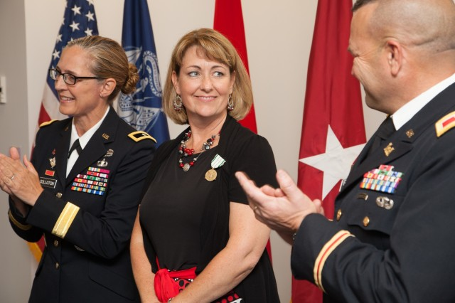 Cheryl Ray, wife of Col. David Ray, receives the Army Public Service Commendation Medal from Brig. Gen. Kim Colloton, U.S. Army Corps of Engineers South Pacific Division commander, during a July 11, 2019, ceremony in Sacramento, Calif. Later that morning, Col. Ray relinquished command of the Sacramento District after leading the unit for three years. Ray then retired from the Army after a 28-year career that included combat deployments and worldwide assignments as an engineer platoon leader, a battalion operations and executive officer, and battalion commander. (U.S. Army photo by Ken Wright)