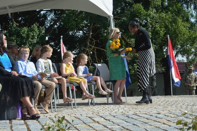 Meagan Condrey accepts a bouquet of yellow roses welcoming her to USAG Stuttgart from Dr. Kaffie Clark, USAG Stuttgart Employee of the Year, as the Condrey children watch. The daughters also received a yellow rose each and the son a garrison challenge coin, July 10, 2019.