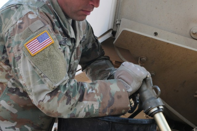 Sgt. Alaor Viera, Headquarters Service Company, 960th Brigade Support Battalion, Wyoming Army National Guard, fuels a truck on Camp Guernsey, Wyoming for soldiers from the 1742nd Transportation Company, South Dakota Army National Guard. The 960th BSB lent support to the South Dakota unit during Operation Golden Coyote, June 2019.