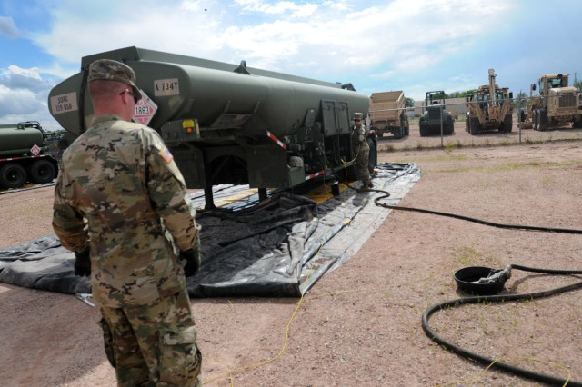 Spc. Jonathan Richards and Pvt. Annabelle Mowery, Headquarters Service Company, 960th Brigade Service Battalion, Wyoming Army National Guard, coordinate fueling at the unit's 5,000-gallon fuel tanker during annual training on Camp Guernsey, June 16, 2019. The 960th supported the South Dakota Army National Guard during their visit, as part of the Operation Golden Coyote training exercise.