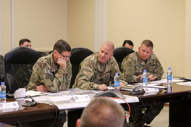 KANDAHAR AIRFIELD, Afghanistan (July 25, 2018) -- U.S. Army Gen. Joseph Votel, left, commander for U.S. Central Command, U.S. Army Brig. Gen. Jeffrey Smiley, middle, commander for Train, Advise and Assist Command-South, and U.S. Army Command Sgt. Maj. Anton Hillig, right, senior enlisted leader for TAAC-South, discuss the capabilities of TAAC-South, July 25, 2018, during Votel's visit to Kandahar Airfield, Afghanistan. (U.S. Army photo by Maj. John Shin)
