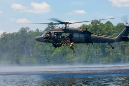 U.S. Army Reserve Soldiers jump out of a UH-60 Blackhawk, while fellow Soldiers swim to shore, as part of a Helocast event at the 2019 U.S. Army Reserve Best Warrior Competition at Fort Bragg, N.C., June 27, 2019.
