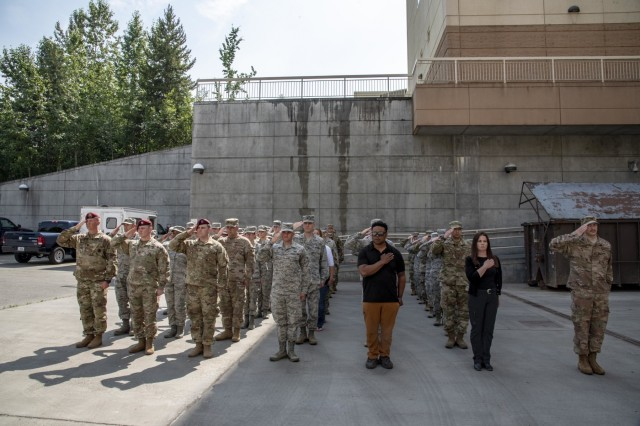 Service members assigned to Joint Base Elmendorf-Richardson, Alaska, and Armed Forces Medical Examiner System medicolegal investigators, stand in formation during a dignified departure at the 673rd Medical Group for remains found on Colony Glacier July 1.