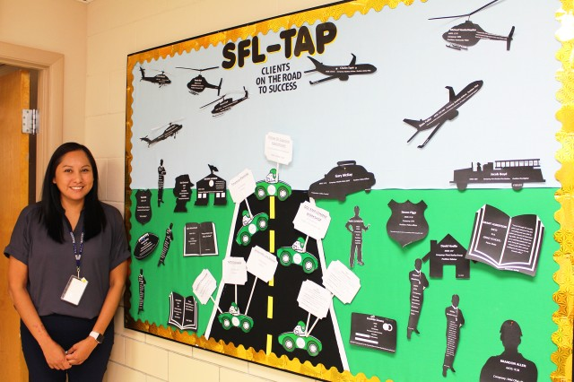 Arlena Gonzales, administrative specialists at the Soldier for Life Transition Assistance Program center, stands next to the success story bulletin she created and maintains to show the different types of employment Soldiers have found using the program.