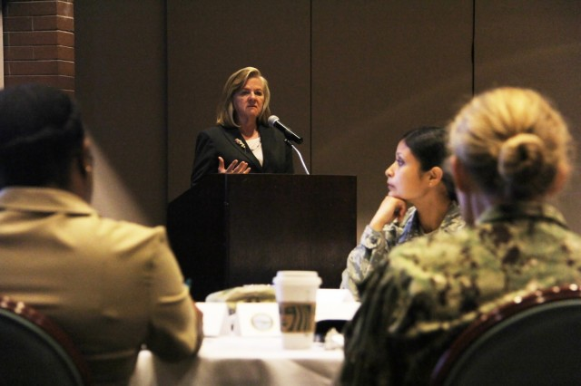 Jane Hourigan, J5 QPP Planning Team, Defense Health Agency, speaks to a crowd of Puget Sound Military Health System members and partners during the recent Quadruple Aim Performance Plan Executive Session at Joint Base Lewis-McChord, Washington.