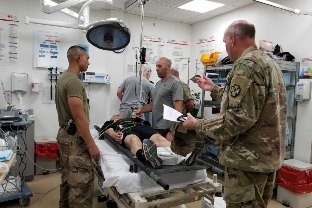 Medical Provider Maj. Anthony Cauchi and Combat Medic Spc. Alfredo Samarripa of the 349th Combat Support Hospital review patient injuries during a mass casualty exercise at the United States Military Hospital - Kuwait, July 13, 2019.