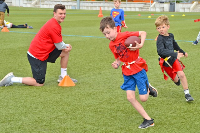 Danny Kapps (left), an Adelphi University graduate student, encourages participants during a session of the Child and Youth Services' Flag Football summer sports camp.