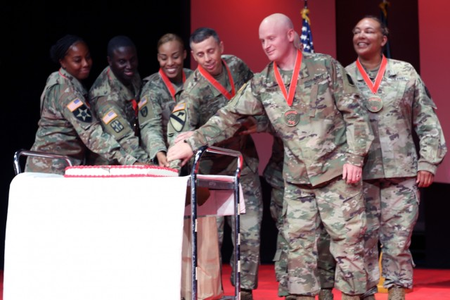 (From left to right) Sergeant 1st Class Natasha Carroll, 16th Sustainment Brigade; Sergeant 1st Class Joseph Stephens, 30th Medical Brigade; Sergeant 1st Class Cherrice Rolax, 30th Medical Brigade; Command Sgt. Maj. Rocky L. Carr, 21st Theater Sustainment Command; Sergeant 1st Class Justin Engle, 10th Army Air Missile Defense Command; and Master Sgt. Natali Christensen, Landstuhl Regional Medical Center - Europe; cut a cake to celebrate their induction to the Sergeant Morales Club, during an induction ceremony, July 10 at the Kleber Kaserne Theater in Kaiserslautern, Germany.(Not pictured) Command Sgt. Maj. Gary E. Plotnick, 10th AAMDC senior enlisted advisor was also inducted into the program but did not cut the cake.