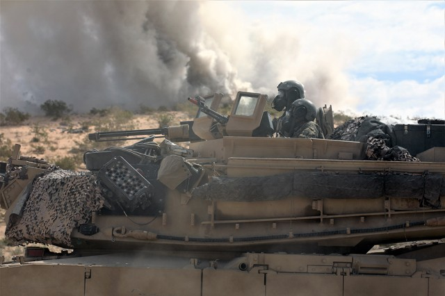 Sgt. Earnest Jarman (bottom) and 2nd Lt Steven Chelton (top), both assigned to the 1-252 Armor Regiment, 30th Armored Brigade Combat Team move to a safe location after a chemical attack by the opposing force in the Mojave Desert during their 19-09 rotation at the National Training Center (NTC) on July 12, 2019. The NTC is a training facility designed to simulate real-life combat scenarios testing warriors' readiness utilizing their military occupational specialty in a high-up-tempo environment. Operation Hickory Sting provides the best, toughest and most current combat training available in the U.S. Army preparing the 30th ABCT for deployment overseas later this fall.