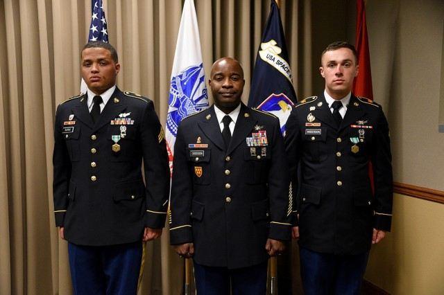 Command Sgt. Maj. Finis Dodson, U.S. Army Space and Missile Defense Command/Army Forces Strategic Command command sergeant major, center, stands with SMDC's 2019 Best Warriors, Sgt. Chayse Burns, left, and Spc. Tanner Anderson, right, July 12 at the command's Peterson Air Force Base, Colorado, headquarters following the ceremony announcing their wins. Burns is assigned to Headquarters and Headquarters Company, 53rd Signal Battalion, 1st Space Brigade, Fort Carson, Colorado, and Anderson is assigned to Company C, 53rd Signal Battalion, Landstuhl, Germany. (U.S. Army photo by Carrie David Campbell)