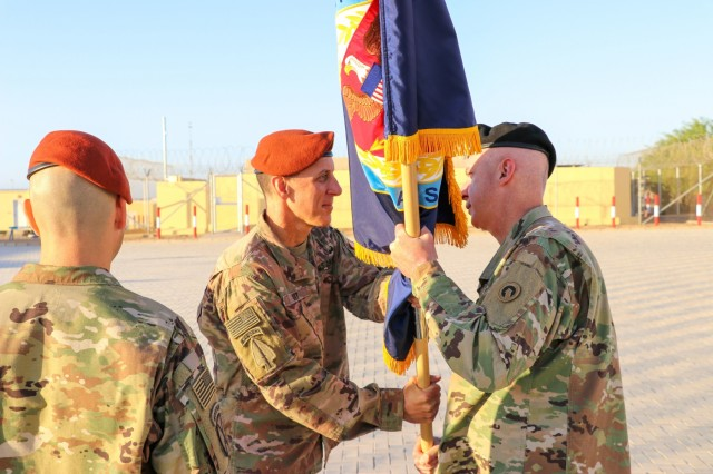 U.S. Army Col. Mark P. Ott, the outgoing commander of Task Force Sinai (TFS), passes the TFS colors to Maj. Gen. John P. Sullivan, commander of the 1st Theater Sustainment Command, during a change of command ceremony at South Camp, Egypt, July 15, 2019. (U.S. Army photo by Staff Sgt. Kulani J. Lakanaria)