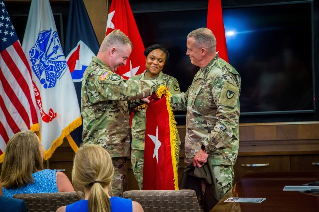 Maj. Gen. Chris Mohan unfurls his new two-star flag during his promotion ceremony July 11 at Army Materiel Command Headquarters, Redstone Arsenal, Ala. Assisting him are Master Sgt. Happiness Brown of AMC G-3 and AMC Command Sgt. Maj. Rodger Mansker.