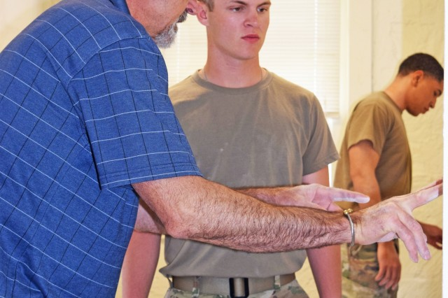 Russell Werth, self-help instructor, shows Pvt. Braxton Webber a detail on the patch he was putting on a sheetrock panel, While Spc. Justin Neely worked on his patch. The two 1st Infantry Division Artillery Soldiers were part of a week-long class to learn how to make repairs at their barracks.