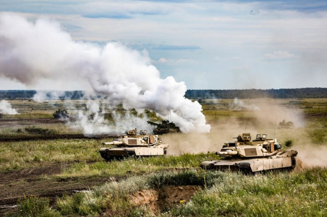 "U.S. and Polish forces participate in a simulated tank battle  during the ""Tank Battle"" event held at Below Piskie Training Area, July 13."