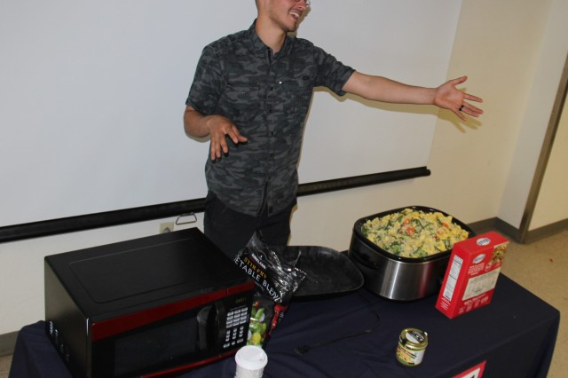 Spc. Norman Serrano, a mechanic with 1-5 Infantry, G. Company, answers a question from the audience during a cooking demonstration June 14 at Barracks 1001. Serrano encourages fellow soldiers to not use living in the barracks as an excuse to eat unhealthy meals.