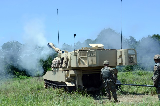 An M109 Paladin self-propelled howitzer fires as AIT students prepare to reload it on the right during a Field Artillery School exercise at Fort Sill, Okla., June 19, 2019.