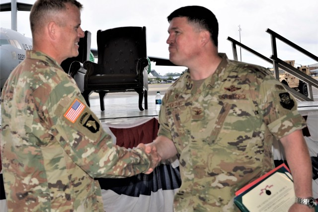Command Sgt. Maj. Timothy Marble, Joint Base Lewis-McChord Garrison command sergeant major, congratulates Col. William Percival, outgoing JBLM Garrison deputy commander and 627th Air Base Group commander, after an awards ceremony at McChord Field July 15.