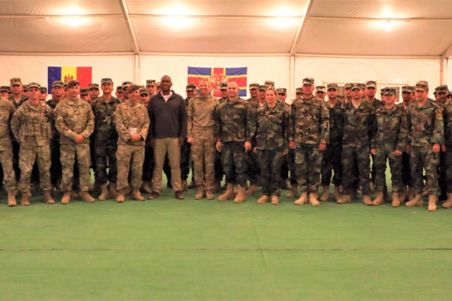 U.S. Ambassador to the Republic of Moldovan, the Honorable Dereck Hogan (civilian clothes center), Commanding General of the National Training Center, Army Maj. Gen. Jeffrey Broadwater (center right), Moldovan Minister of Defense, Pavel Voicu (right of MG Broadwater) and Moldovan and U.S. Army soldiers assigned to the 1st Security Force Assistance Brigade pose for a photo during the 30th Armored Brigade Combat Team's NTC rotation 19-09, July 16, 2019. For over three weeks in the sweltering Mojave Desert heat, the Moldovan scout unit has trained side-by-side with their longtime National Guard State Partner, NC National Guard's 30th Armored Brigade Combat Team, as well as with the 1st Security Force Assistance Brigade. They conducted joint unit specific training and combined arms maneuver and collective gunnery with National Guard troops from North Carolina, South Carolina, West Virginia and Ohio.