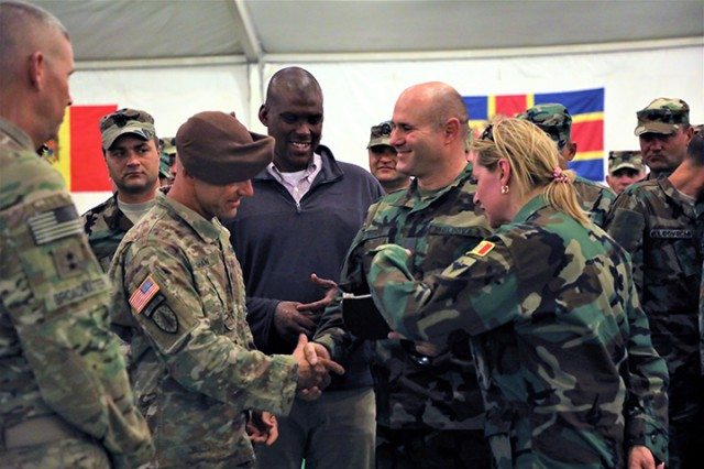 Moldovan Army Col. Mariana Grama (right), Minister of Defense of Moldova Pavel Voicu (center right), U.S. Ambassador to the Republic of Moldova, the Honorable Dereck Hogan (center) and U.S. Army Capt. Justin Shaw, 1st Security Force Assistance Brigade (with beret), exchange handshakes and awards during the 30th Armored Brigade Combat Team's rotation 19-09, at NTC, Fort Irwin, California. For over three weeks in the sweltering Mojave Desert heat, the Moldovan scout unit trained side-by-side with their longtime National Guard State Partner, NC National Guard's 30th Armored Brigade Combat Team, as well as with the 1st Security Force Assistance Brigade.