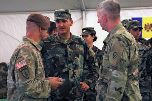 U.S. Army Capt. Justin Shaw (left), assigned to the 1st Security Force Assistance Brigade, Moldovan Army Maj. Alexandr Procopciuc (center), the Moldovan Army Reconnaissance Company Commander and NC Army National Guard's, Maj. Patrick Mohan (right), Bilateral Affairs Officer with Moldova, speak about the training conducted by the Moldovan scouts during the 30th Armored Brigade Combat Team's NTC rotation 19-09, on July 16, 2019. For over three weeks in the sweltering Mojave Desert heat, the Moldovan scout unit has trained side-by-side with their longtime National Guard State Partner, NC National Guard's 30th Armored Brigade Combat Team, as well as with the 1st Security Force Assistance Brigade.