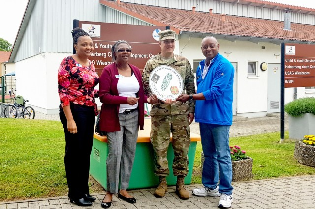 U.S. Army Garrison Wiesbaden Commander Col. Noah Cloud presents a Green Boot award to the Hainerberg Child Development Center staff June 6 outside the center. The Army Lodge also received the award. The Green Boot designation recognizes organizations for their efforts to conserve energy and resources.