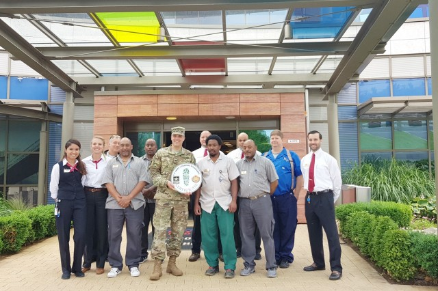 U.S. Army Garrison Wiesbaden Commander Col. Noah Cloud presents a Green Boot award to the Wiesbaden Lodge staff June 6 outside the lodge. The Hainerberg Child Development Center also received the award. The Green Boot designation recognizes organization's efforts to conserve energy and resources.