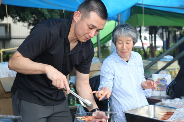 Staff Sgt. David Shores, left, assigned to the 38th Air Defense Artillery Brigade, grills hot dogs at a festival July 14 at Aioi Park near Sagami General Depot. Four Soldiers from the 38th ADA volunteered to provide support at the festival as a way to reinforce the relationship the Army shares with its nearby neighbors outside the gate at Sagami Depot.