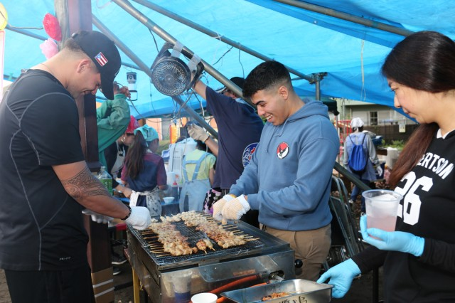 "Spc. Allan Abreu, left, and Pvt. Jose Muniz Santiago, right, grill chicken skewers known as ""yakitori"" at a festival July 14 at Aioi Park near Sagami General Depot. Four Soldiers from the 38th ADA volunteered to provide support at the festival as a way to reinforce the relationship the Army shares with its nearby neighbors outside the gate at Sagami Depot."