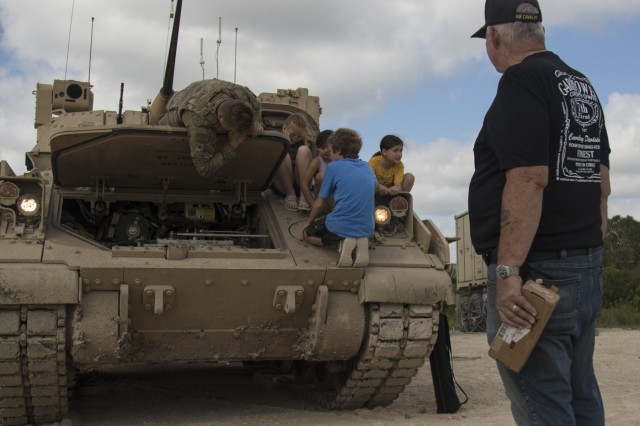 Spc. Connor Loftin, 1st Squadron, 7th U.S. Cavalry Regiment, shows the inside of a Bradley Fighting Vehicle at the Garryowen Family Day on July 17, 2019, Fort Hood, Tx. Families of Soldiers and veterans were given the opportunity to see how Soldiers operated in a tactical environment at the event. (U.S. Army photo by Pfc. Alisha Edwards, 7th Mobile Public Affairs Detachment)