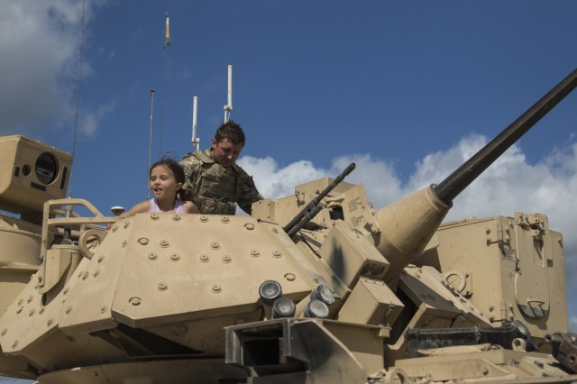Spc. Austin Snider, 1st Squadron, 7th U.S. Cavalry Regiment, helps a young girl explore the inside of a Bradley Fighting Vehicle at the Garryowen Family Day on July 17, 2019, Fort Hood, Tx. Families of Soldiers and veterans were given the opportunity to see how Soldiers operated in a tactical environment. (U.S. Army photo by Pfc. Alisha Edwards, 7th Mobile Public Affairs Detachment)
