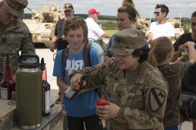 Sgt. Jenna Michelle Trevino, 1st Squadron, 7th U.S. Cavalry Regiment, serves snow cones at the Garryowen Family Day on July 17, 2019, Fort Hood, Tx. Families of Soldiers and veterans were given the opportunity to see how Soldiers operated in a tactical environment at the event. (U.S. Army photo by Pfc. Alisha Edwards, 7th Mobile Public Affairs Detachment)