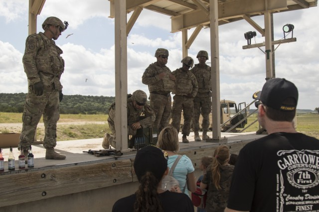 Soldiers of the 1st Squadron, 7th U.S. Cavalry Regiment, speak to the attendees of the Garryowen Family Day on July 17, 2019, Fort Hood, Tx. Families of Soldiers and veterans were given the opportunity to see how Soldiers operated in a tactical environment. (U.S. Army photo by Pfc. Alisha Edwards, 7th Mobile Public Affairs Detachment)