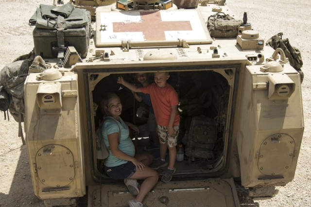 The family of Sgt. Aaron Hannsberry explores a medical vehicle during the 1st Squadron, 7th U.S. Cavalry Regiment Garryowen Family Day on July 17, 2019, Fort Hood, Tx. Families of Soldiers and veterans were given the opportunity to see how Soldiers operated in a tactical environment. (U.S. Army photo by Pfc. Alisha Edwards, 7th Mobile Public Affairs Detachment)
