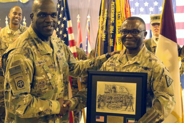 Command Sgt. Maj. Bernard Small, 1st Theater Sustainment Command, presents Command Sgt. Maj. Ekondua Amoke, 8th Medical Brigade, with a plaque before a transfer of authority ceremony between 8th Medical Brigade and 3d Medical Command Deployment Support - Forward at Camp As Sayliyah, Qatar, July 18, 2019. (U.S. Army National Guard photo by Sgt. Connie Jones)