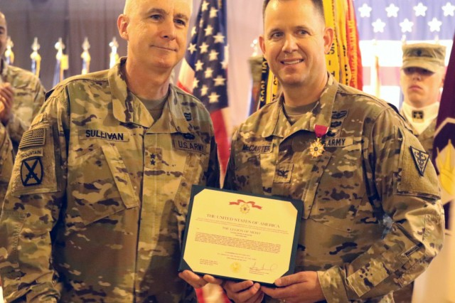 Maj. Gen. John P. Sullivan, commanding general of 1st Theater Sustainment Command, presents Col. Jeffrey McCarter, 8th Medical Brigade commander, with the Legion of Merit award before a transfer of authority ceremony between 8th Medical Brigade and 3d Medical Command Deployment Support - Forward at Camp As Sayliyah, Qatar, July 18, 2019. (U.S. Army National Guard photo by Sgt. Connie Jones)